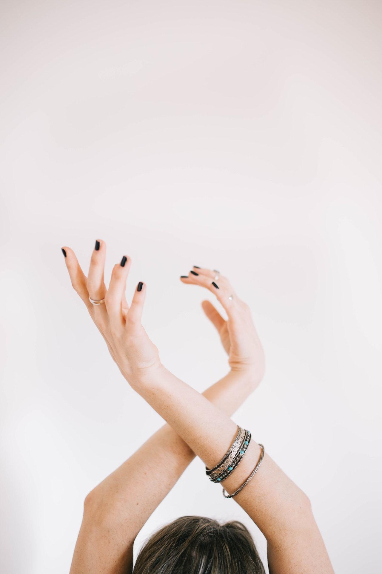 ruce nad hlavou s náramky a prsteny