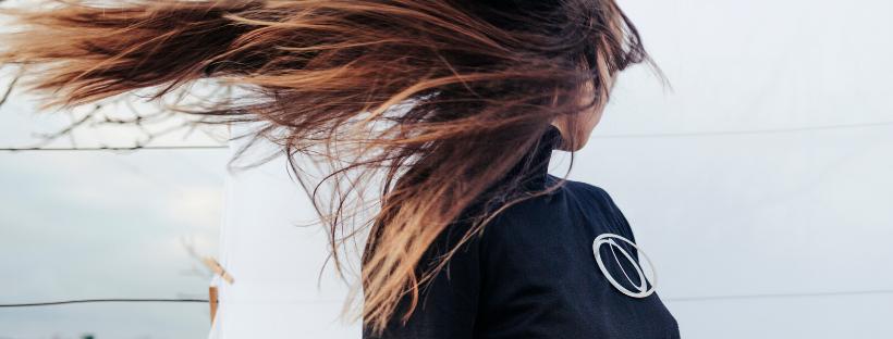 dívka s rozevlátými vlasy a šperkem - designovou broží